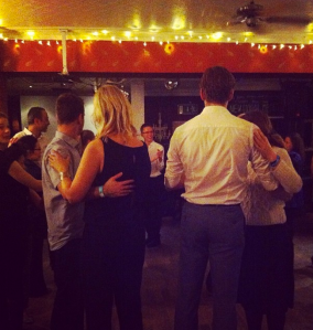 Couples learn how to salsa as they watch the dance tutors.